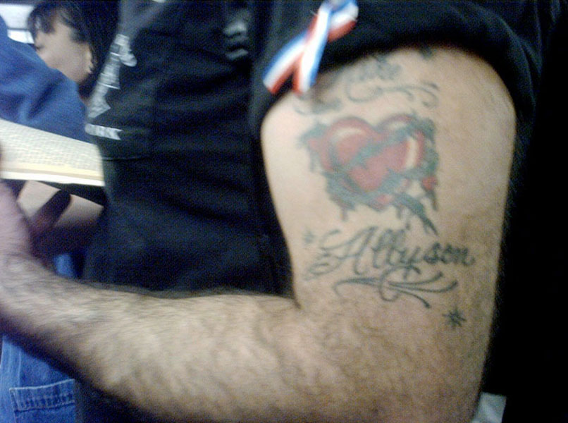 patriotic ribbon-twist and tender tattoo on a muscular arm