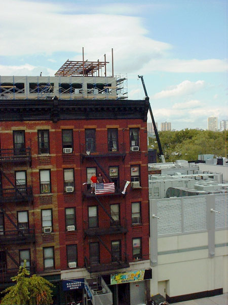 display of flags on tenemant fire escape in Hell's kitchen, New York City
